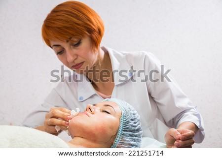 Beautiful woman with facial mask at beauty salon.Pretty woman receiving facial massage.Spa therapy for young woman receiving facial mask at beauty salon - indoors - stock photo