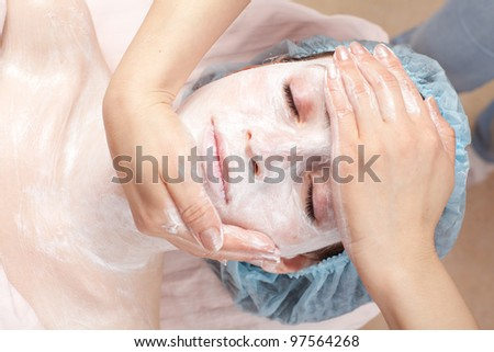 Beautiful woman with facial mask getting beauty treatment at salon - stock photo