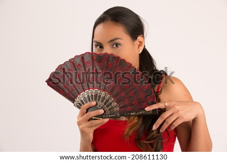 Beautiful woman with fan covering her face