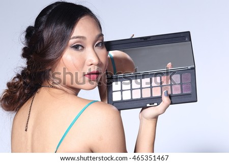 Beautiful Woman with fashion make up and perfect skin Portrait holding Cosmetic Palette