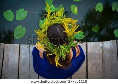 Beautiful woman with  flower diadem near the lake - stock photo