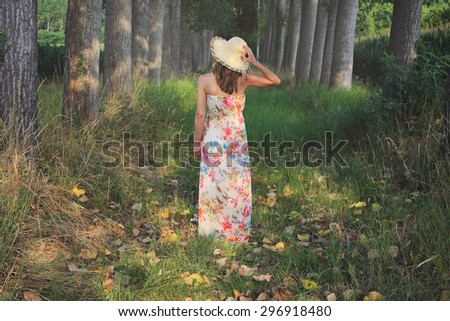 Beautiful woman with flowered dress and summer hat - stock photo