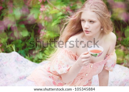 Beautiful woman with flowering tree drinking tea - stock photo