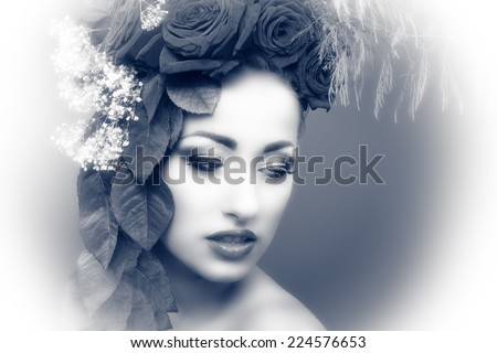 Beautiful woman with flowers and leafs in her hair. She is in a very emotional mood.