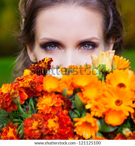 Beautiful woman with flowers in autumn park - stock photo