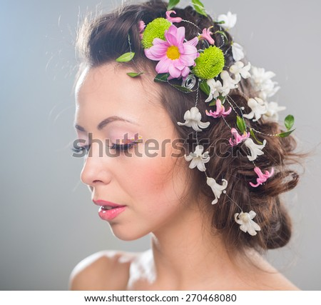 Beautiful woman with flowers in hair. - stock photo