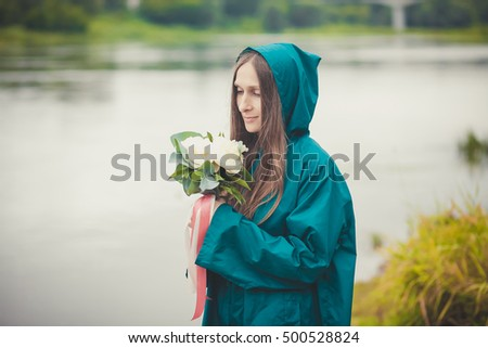 beautiful woman with flowers in raincoat on the background of the river .