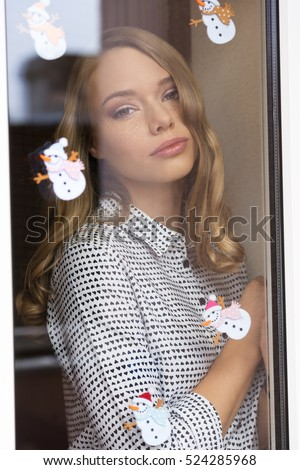 beautiful woman with freckles and long blonde hair behind window pane decorated with small snowman stickers. Fashion romantic portrait in winter time