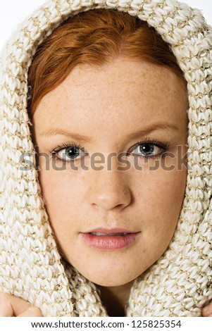 Beautiful woman with freckles and red hair.  She has a warm scarf wrapped around her head. - stock photo