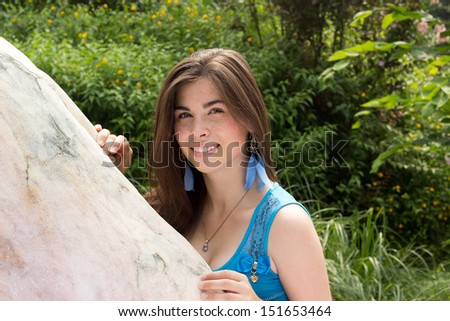 Beautiful woman with freckles hiding behind rock in green nature background - stock photo