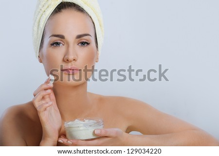 Beautiful woman with fresh health skin applying female cream after spa procedures - stock photo