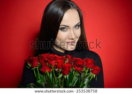 Beautiful Woman with Fresh Red Roses. Girl and Flowers over Red Background. Beauty Female Face. Happiness, Freshness, Beauty, Youth. - stock photo