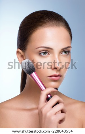 Beautiful woman with fresh skin holding brush for makeup - stock photo