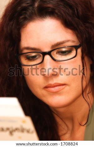 Beautiful woman with glasses reading - stock photo