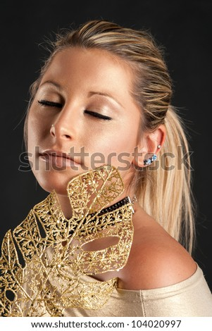 Beautiful woman with golden make up against black background.