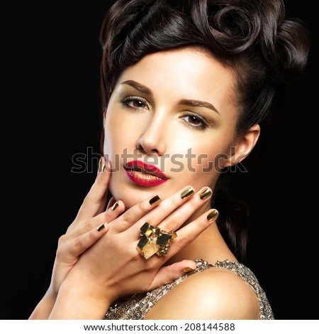 Beautiful  woman with golden nails and fashion makeup of eyes. Brunet girl model with style manicure on black background - stock photo
