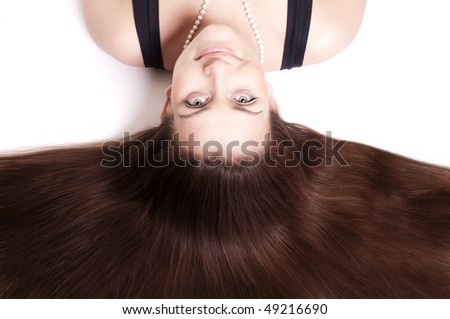 Beautiful woman with gorgeous dark hair. Upside down. Isolated on white. - stock photo