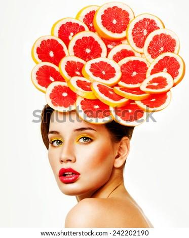 Beautiful woman with grapefruit slices. Citrus. Perfect skin. Professional makeup. - stock photo