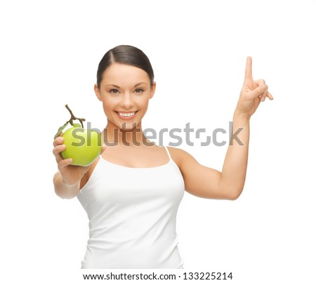 beautiful woman with green apple pointing her finger up. - stock photo