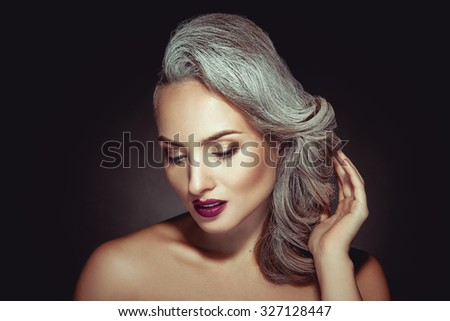 Beautiful woman with grey hair color and nice makeup in studio