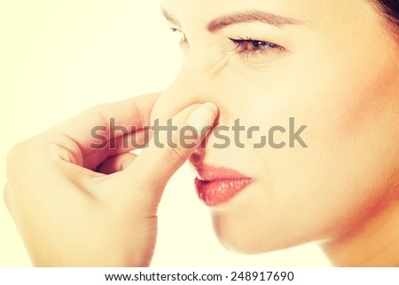 Beautiful woman with grimace because of bad smell. - stock photo