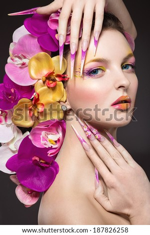 Beautiful woman with hair made of flowers and long nails - stock photo