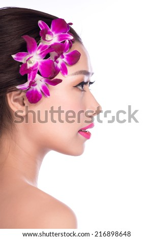 Beautiful woman with hairstyle, bright makeup, manicure. With violet orchid flowers