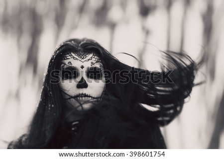 Beautiful woman with halloween sugar skull make-up at winter. Makeup girl like sugar skull - a symbol of Day of the Dead holiday. Symbolism to celebrate Day of the Dead. Black and white photo.  - stock photo