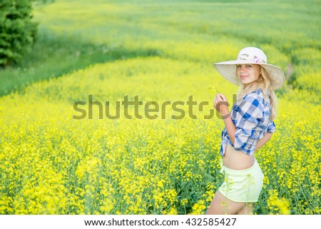 Beautiful woman with hat on head standing in rapeseed field