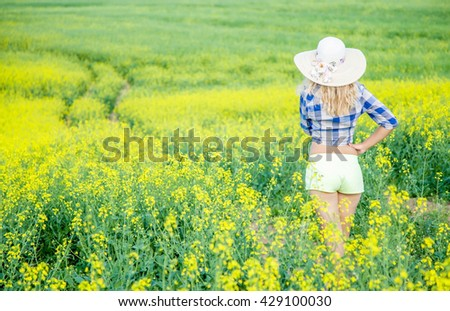 Beautiful woman with hat on head standing in rapeseed field and she looking on the far road and thinking to go or not to go down along the road - stock photo