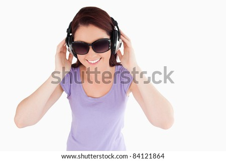 Beautiful Woman with headphones and sunglasses in a studio