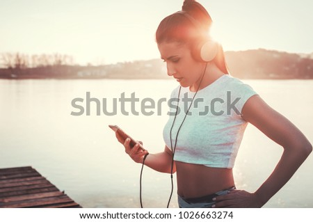 Beautiful woman with headphones listenin to music while workout outdoors