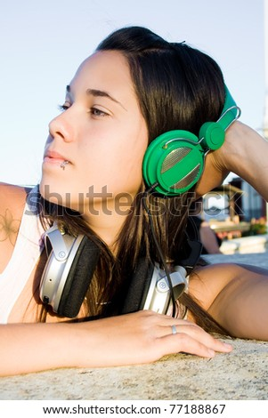 Beautiful woman with headphones on city