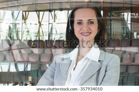 Beautiful woman with headset working in call centre. Portrait in office against of glass reflection