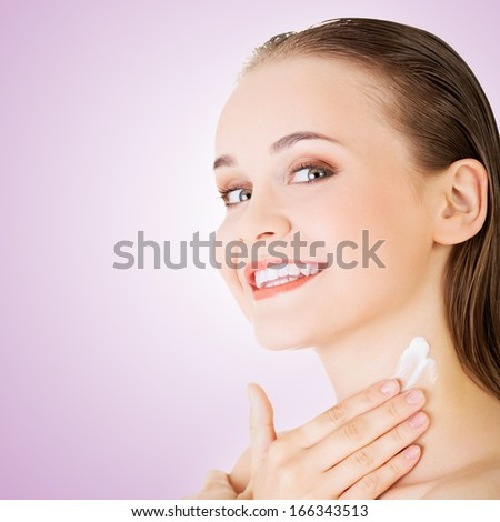 Beautiful woman with healthy skin applying cosmetic cream on a clean fresh face