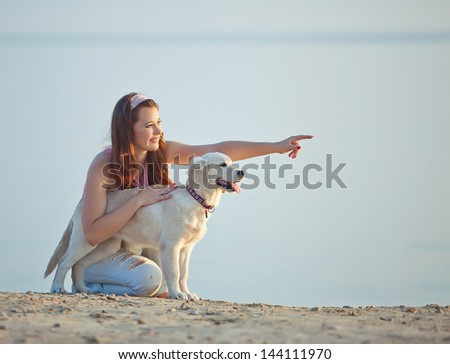 Beautiful woman with her dog playing on the sea shore. - stock photo