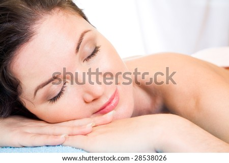 Beautiful woman with her eyes shut having rest in the spa salon