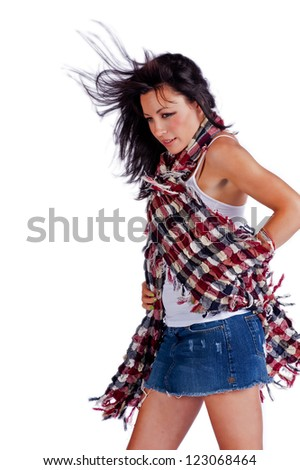 Beautiful woman with her hands on her hips as the wind tries to take control of her scarf.