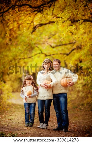 Beautiful woman with her husband and young daughter in autumn garden