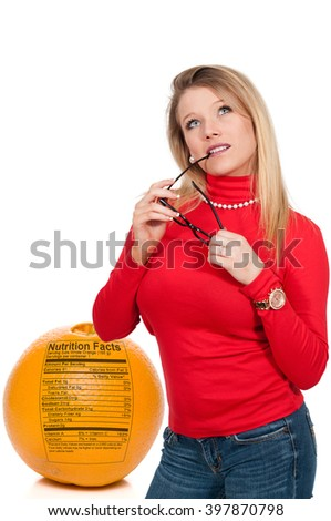 Beautiful woman with her stylish designer glasses standing beside an orange - stock photo