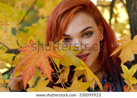 beautiful woman with interesting red hair style and face piercing in autumn scene
