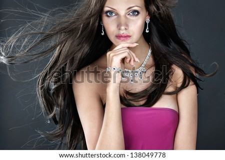 Beautiful woman with jewellery on dark background - stock photo