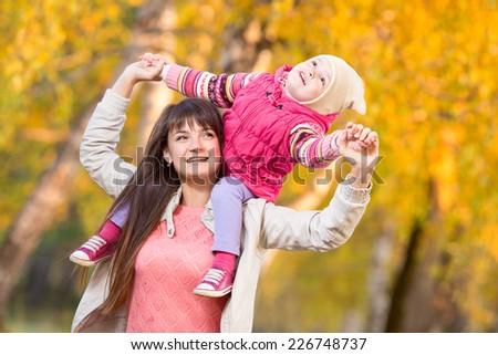 beautiful woman with kid girl outdoors in autumnal park