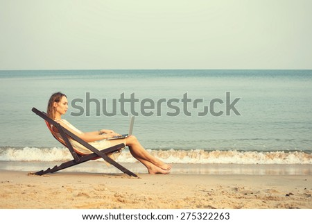 Beautiful woman with laptop computer on the beach. Online shopping, freelance concept