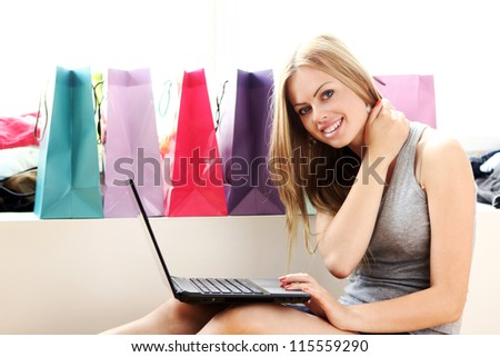 Beautiful woman with laptop on hands and shopping bags behind her