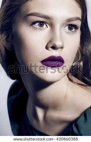 beautiful woman with lilac lips in green dress
