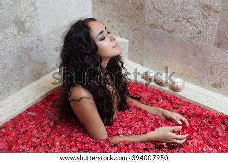 Beautiful woman with long black hair enjoying in marble bath filled leaves of red flowers - stock photo