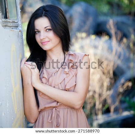 Beautiful woman with long black hair, outdoors shot against a wall.  - stock photo