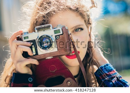 Beautiful woman with long blond curly hair in urban background with vintage camera