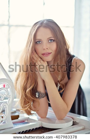 Beautiful woman with long brown hair in black dress leaning the piano - stock photo